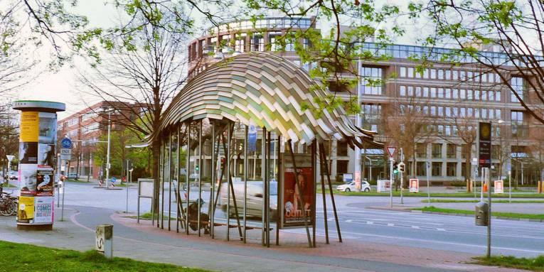 Bushaltestelle mit Dach aus Metallgeflecht.