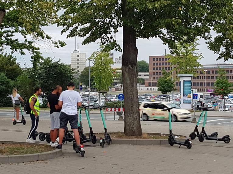 Unter einem Baum stehen Menschen  und Elektroroller
