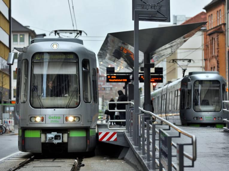 Silberne Stadtbahn hält an Hochbahnsteig