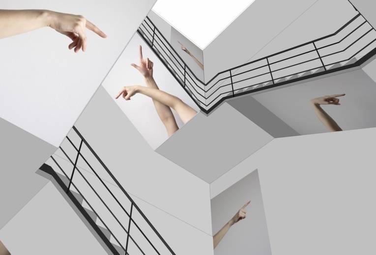 Treppenhaus, in dem Fotografien von zeigenden Armen und Fingern angebracht sind