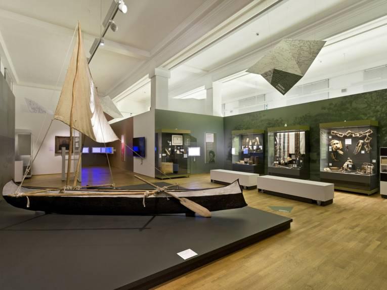 Raum mit Vitrinen und einem Auslegerboot mit Segel