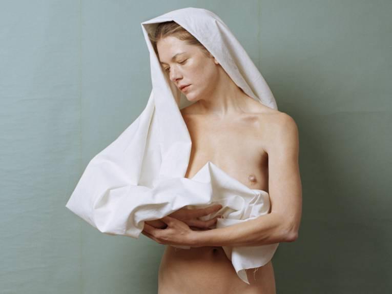 Nackte Frau mit Handtuch über Kopf und Brust hält offenbar ein Kind in den Armen, das aber nicht zu sehen ist.