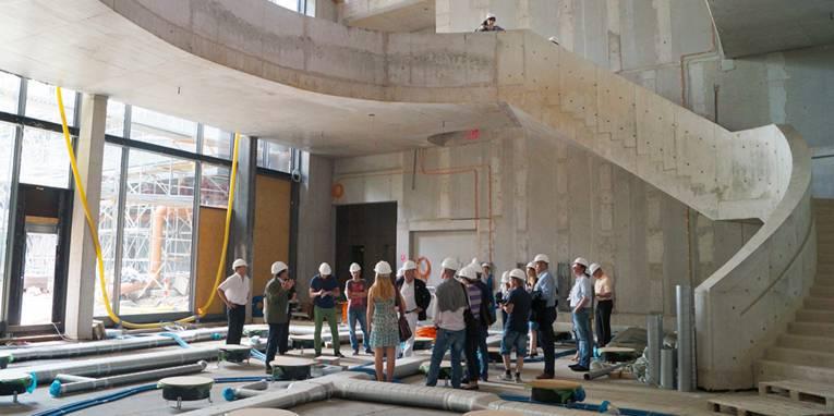 Gruppenführung in großen Halle, die noch eine Baustelle ist.