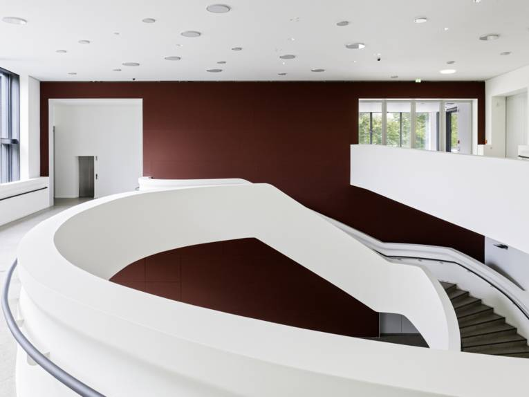 Blick in einen großen zweigeschossigem Raum, in dem ein lang geschwungener runder Aufgang die beiden Etagen miteinander verbindet.