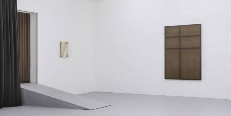 Ausstellungsraum, in dem links eine Rampe zu einem Durchgang mit Vorhang führt. An den zwei sichtbaren Wänden hängen ein großes und ein kleines abstraktes Bild.
