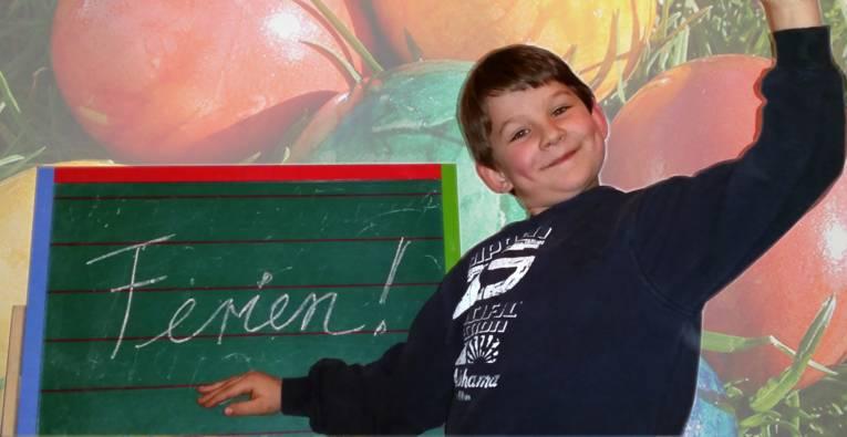"""Junge steht vor einer Tafel, auf der """"Ferien"""" steht."""