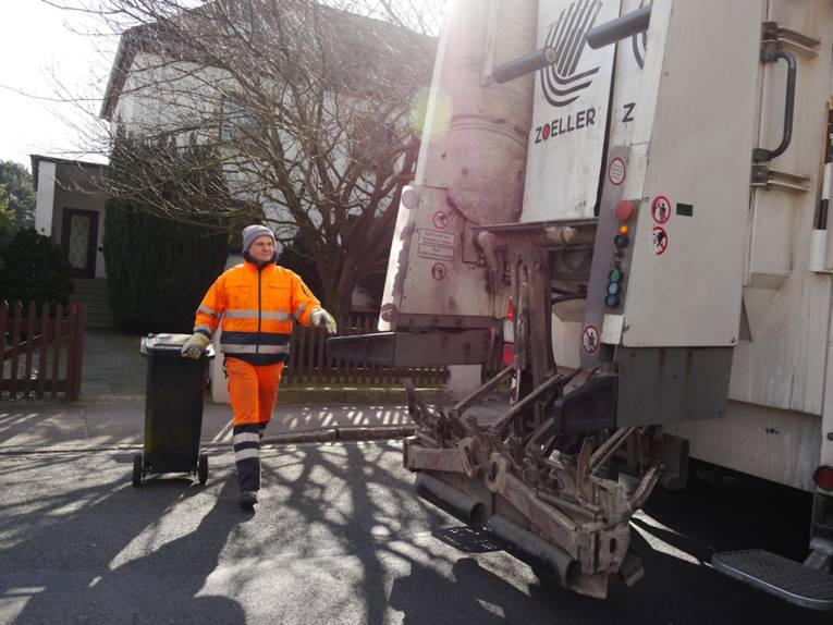 Mann mit Mülltonnen und Müllauto