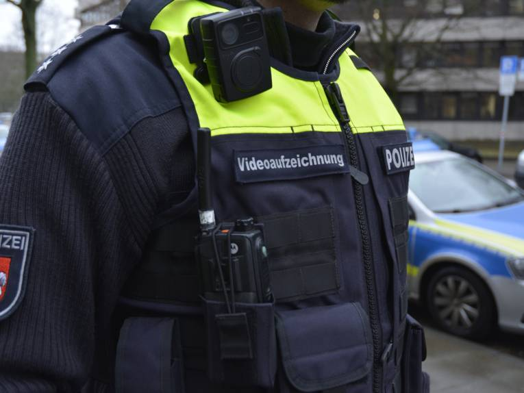 Nahaufnahme eines Polizeibeamten, der eine kleine Kamera am Körper trägt