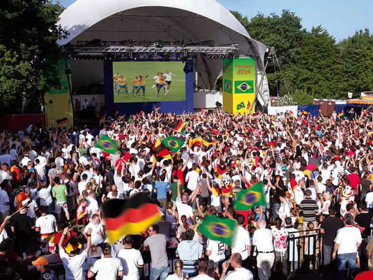 Menschenmenge mit Deutschlandfahnen vor Großbildleinwand.