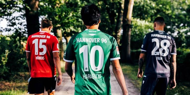 Drei Fußballspieler in Trikots von Hannover 96 von hinten aufgenommen