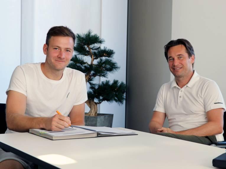 Zwei Männer sitzen an einem Tisch, einer unterschreibt etwas.