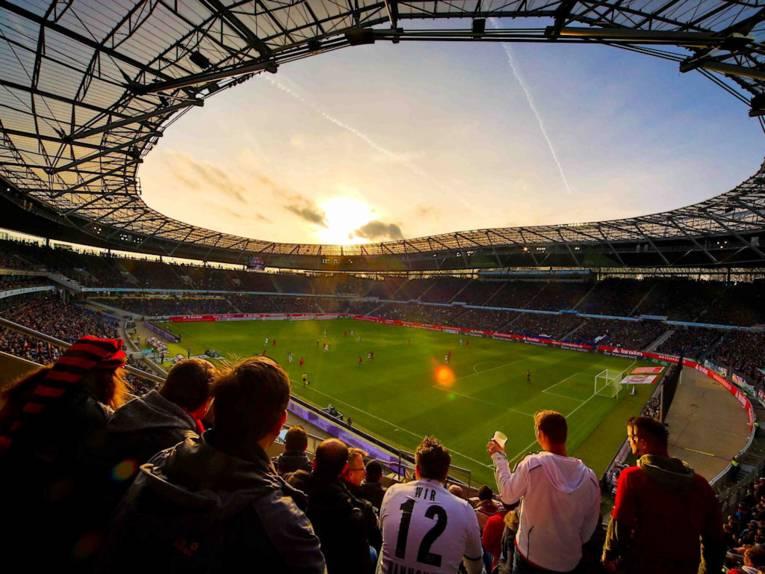 Innenraum eines Fußballstadion im Abendlicht.