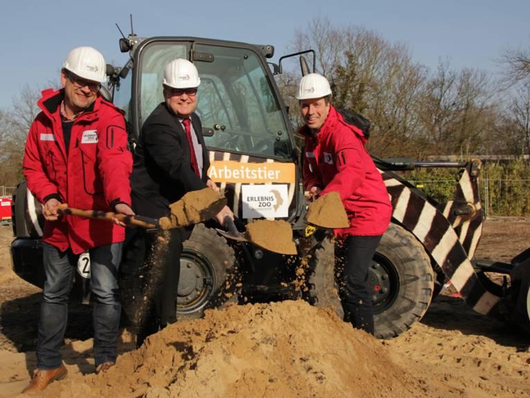 Drei Männer mit Helmen halten jeweils einen Spaten mit Sand in den Händen.