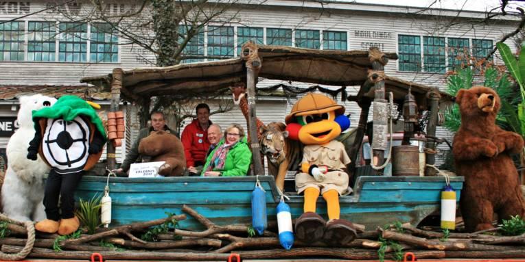 Festumzugswagen, auf dem ein Holzboot und große Tierfiguren angebracht sind.