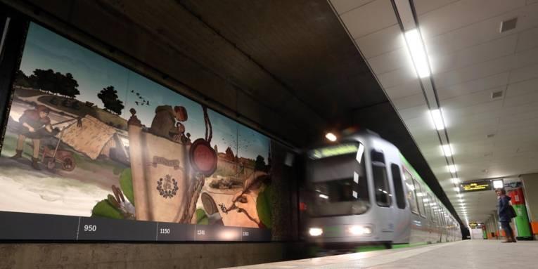 Eine Bild-College an der Wand eines Stadtbahn-Gleises und eine einfahrende Stadtbahn.