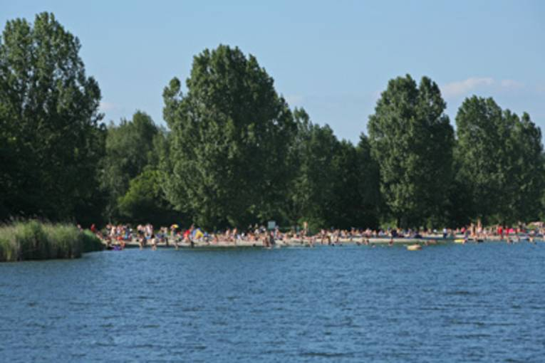 blaues Wasser, im Hintergrund badende Menschen an der Uferzone des Altwarmbüchener Sees