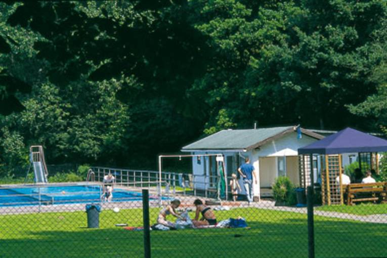 Liegewiese mit zwei Badegästen, im Hintergrund ein Schwimmbecken mit Rutsche, rechts ein Gebäude und ein blauer Gartenpavillion