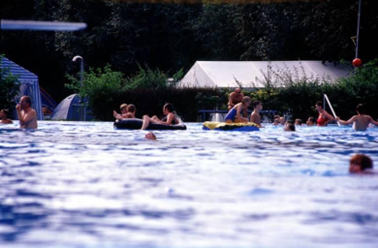 Schwimmende und im Wasser spielende Menschen