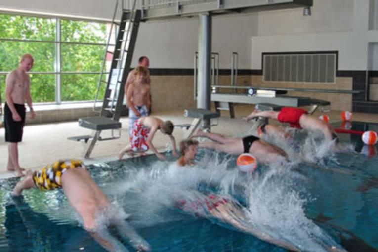 Schwimmer springen mit einem Kopfsprung vom Beckenrand