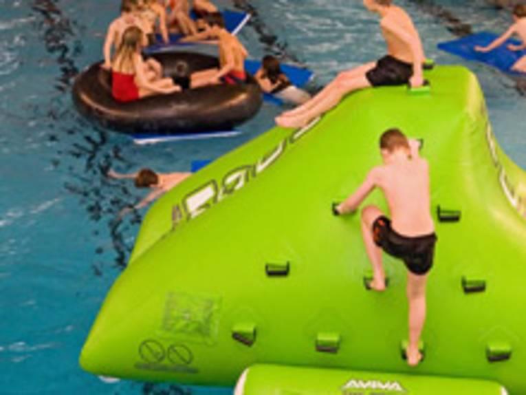 Kinder im Schwimmbad auf einem aufgeblasenen, grünen Berg und auf riesigen Schwimmreifen