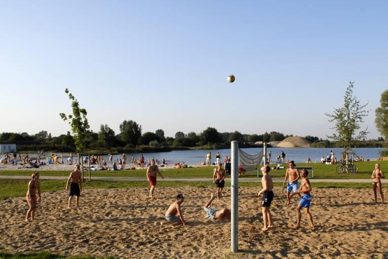 vorne Beachvolleyball spielende Jugendliche, eine Liegewiese, im Hintergrund der See