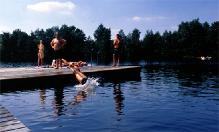 ein Holzbadesteg auf dem Kinder stehen, ein Kind springt gerade mit einem Kopfsprung ins Wasser, im Hintergrund ein Paddelboot