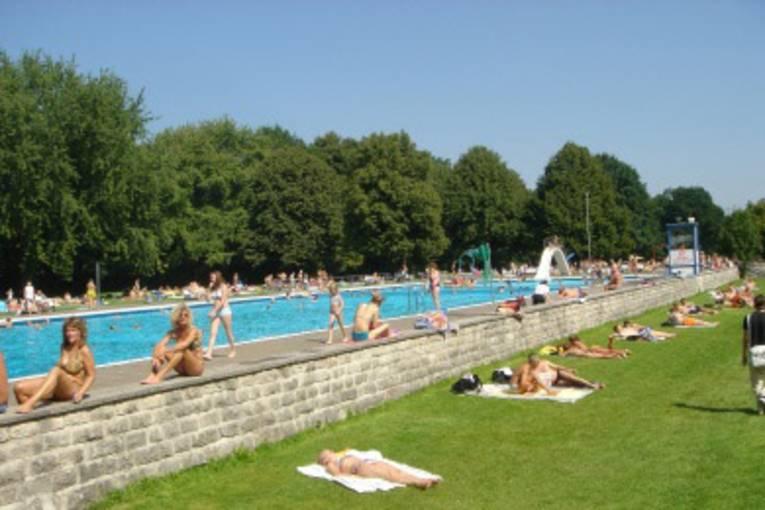 Ein Schwimmerbecken unter freien Himmel mit einigen Badenden. Rechts und links vom Becken Liegewiesen mit sehr vielen Menschen. Bäume im Hintergrund.