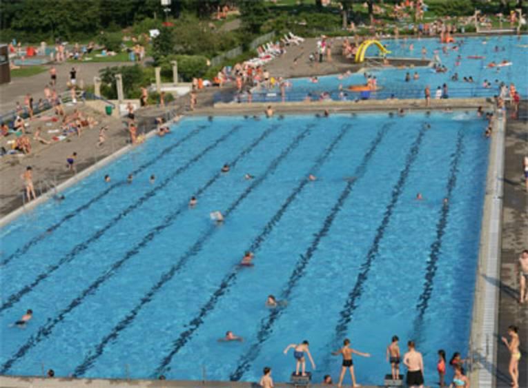 Zwei Schwimmbecken, schwimmende Menschen, im Hintergrund eine gelbe Rutsche