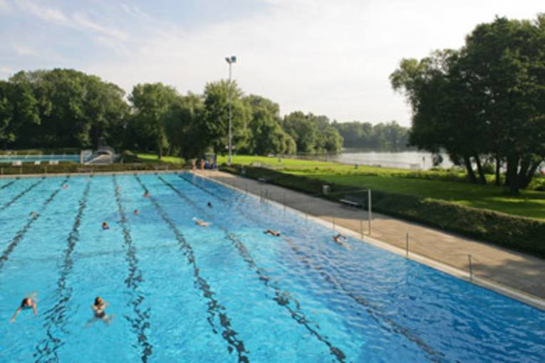 Schwimmerbecken, einige Schwimmer, ein See und Bäume im Hintergrund