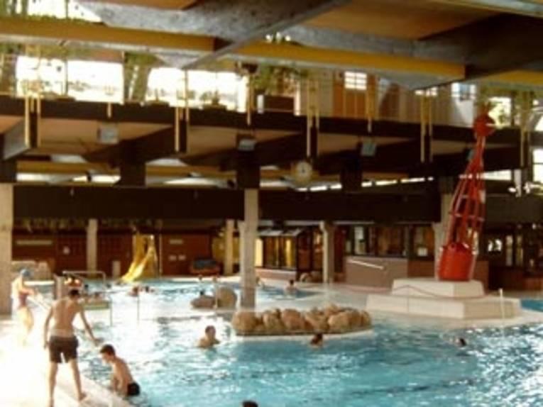 Schwimmer im Becken und am Beckenrand im Vahrenwalder Bad