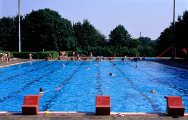 Blick auf das Schwimmerbecken, einige Schwimmer sind im Wasser, im Hintergrund stehen ein paar Menschen am Beckenrand