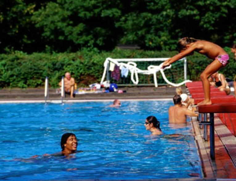 Schwimmerbecken mit einigen Badenden, ein lachender Schwimmer blickt nach rechts zum Beckenrand, wo ein Mädchen ins Wasser springt