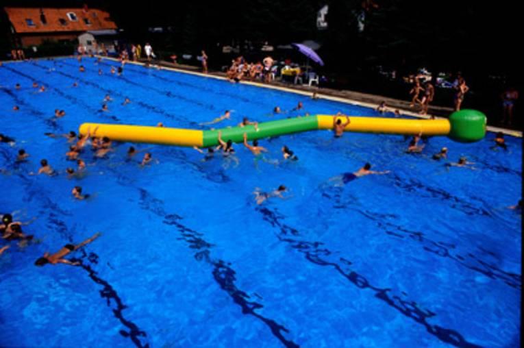 Blick von oben in ein Schwimmbecken, in dem Schwimmbecken befindet sich eine riesige aufgeblasene Raupe aus grünem und gelben Kunststoff, Schwimmer spielen damit und versuchen auf die Raupe zu klettern
