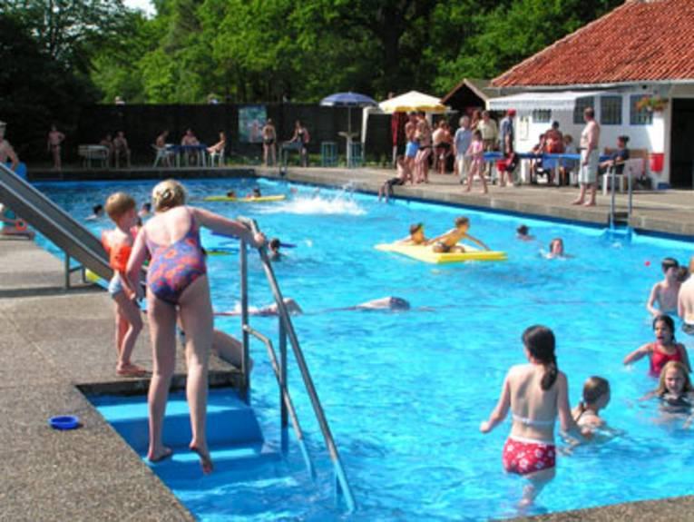 Sonnenschein, eine Frau steht auf der Treppe ins Schwimmbecken, Wasser spielen Kinder, im Hintergrund sieht man Menschen unter einer Markise sitzen, in der Nähe des Beckenrandes stehen Sonnenschirme