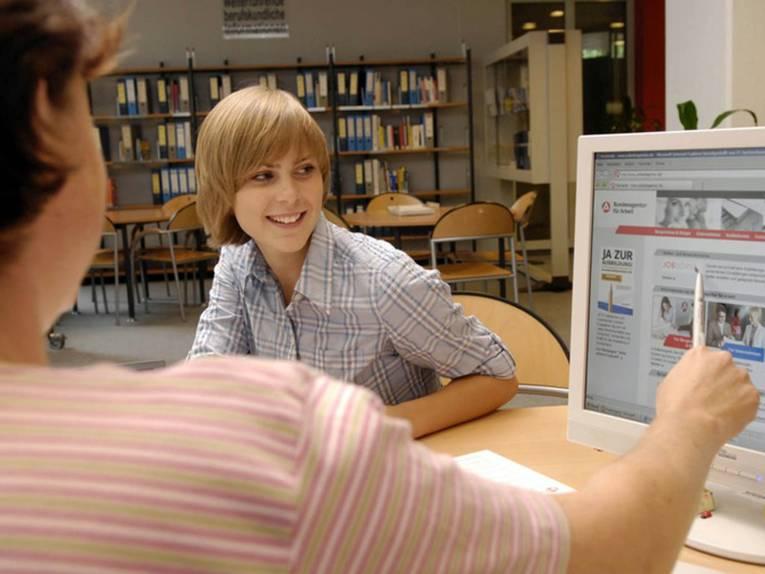 Eine Frau, die nur von hinten zu sehen ist, zeigt einer jungen Erwachsenen, die ihr gegenüber sitzt, etwas auf dem Computerbildschirm.