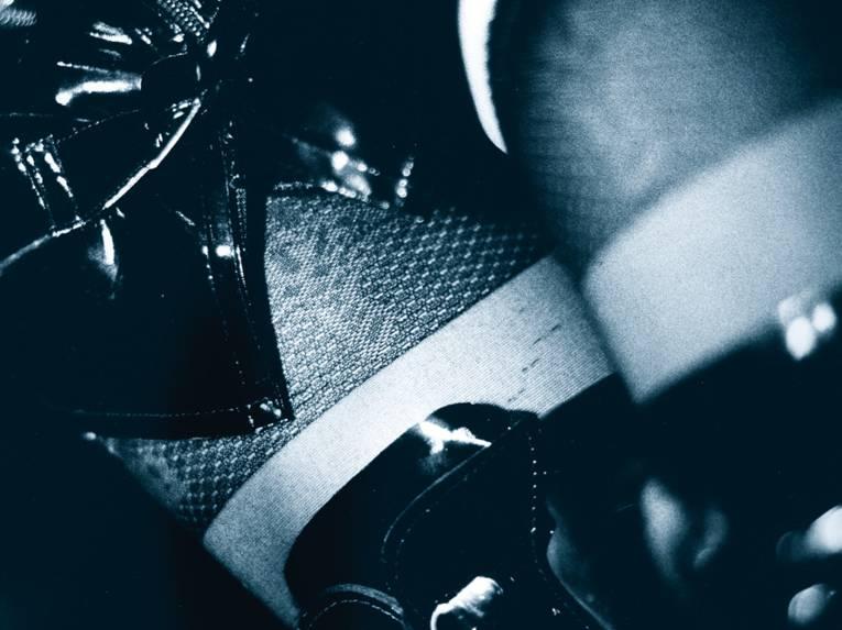 Schwarz-weiss Motiv: Frauenoberschenkel mit schwarzer Strumpfhose, Lackstiefeln und Lackrock