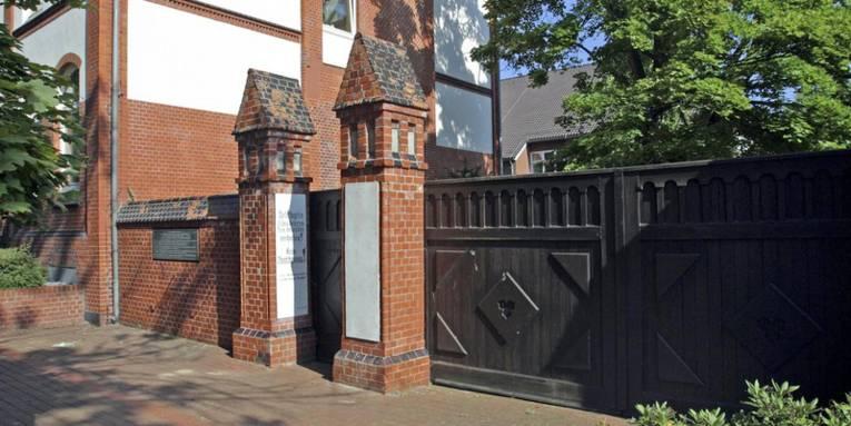 Vor dem Eingang zur Gedenkstätte Ahlem. Teilweise Steinmauer und der Eingang ist zwischen zwei genauerten Säulen, die aussehen wie kleine Türme.
