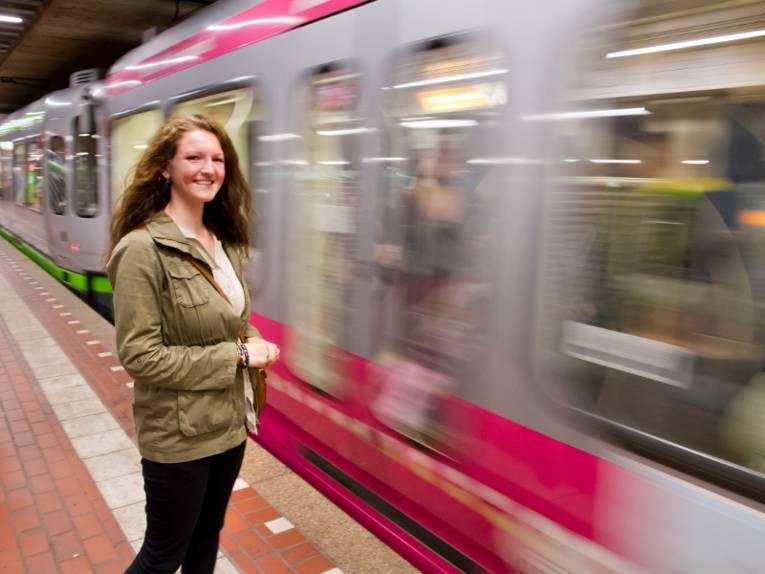 Junge Frau steht in einer U-Bahnstation und eine Bahn fährt ein.