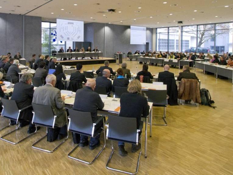 Ein großer Sitzungssaal, in dem in U-Form drei Reihen Tische und Stühle aufgebaut sind, drei Leinwände hängen und ein Podiumsbereich eingerichtet ist. Es tagen hier Mitglieder der Regionsversammlung.