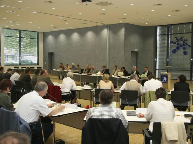 Zwei Reihen mit Tischen und Stühlen, an denen Sitzungsteilnehmer Platz genommen haben und eine Sitzreihe vorne mit mehreren Personen, die in Richtung des Publikums schauen.
