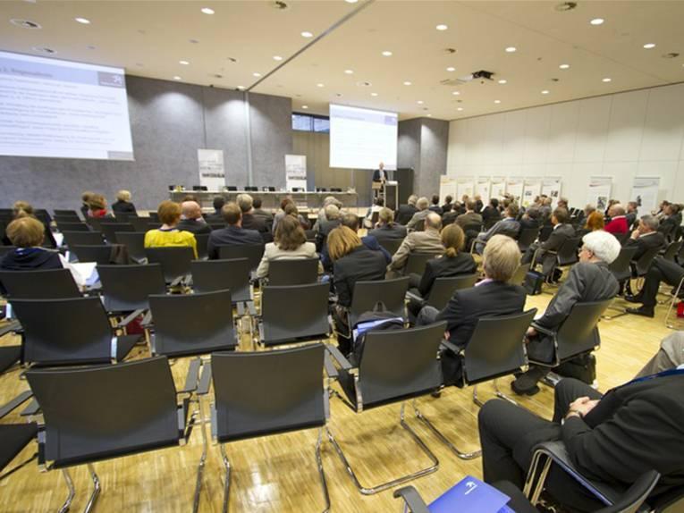 Kinobestuhlung in einem Sitzungsraum mit einigen nicht besetzten Plätzen. Vorne befinden sich zwei Leinwände, ein Podium und ein Pult, an dem gerade ein Redner spricht.