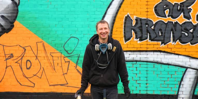 Ein Mann steht mit einer Spraydose vor einem großen Graffiti