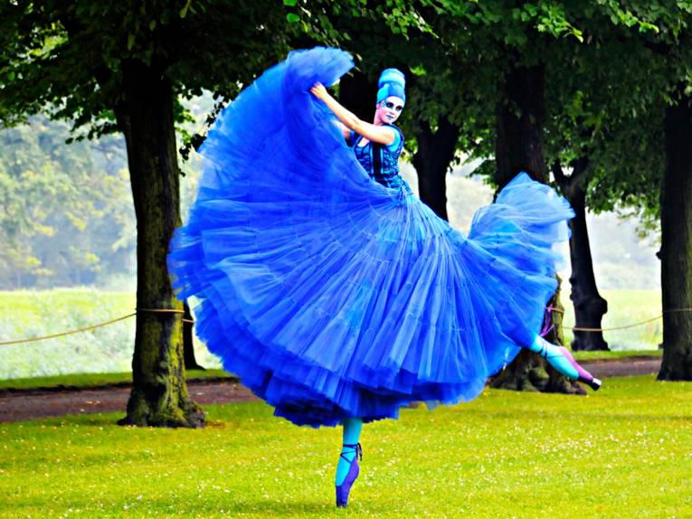 Eine Ballerina in einem blauen Kleid tanzt auf Stelzen durch den Garten