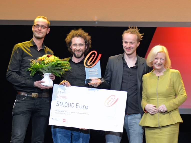 Vier Menschen auf einer Bühne. Sie halten Blumen, eine Trophäe und ein großes Plakat.