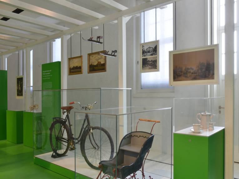 Ein Blick in den Gartenflügel im Museum Schloss Herrenhausen: Ein altes Fahrrad und ein alter Kinderwagen in Glasvitrinen, im Hintergrund diverse Bilder