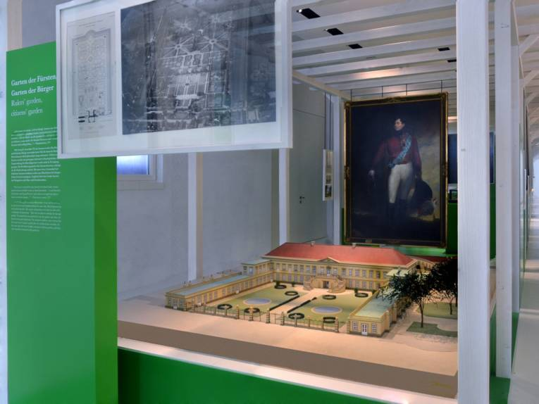 Blick in den Gartenflügel des Museums Schloss Herrenhausen, im Zentrum des Bildes ein Modell des Schlosses aus früheren Zeiten, im Hintergrund hängt ein großformatiges Gemälde