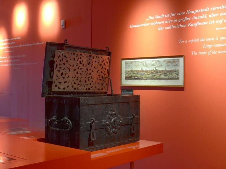 Eine massive Kiste, in der in früheren Zeiten Geld aufbewahrt wurde, inmitten des roten Barockflügels im Museum Schloss Herrenhausen; an der Wand im Hintergrund hängt ein Stich, der Hannover im Mittelalter zeigt