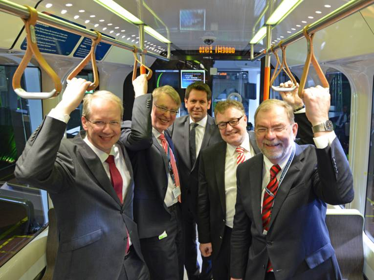 Fünf Männer stehen in Stadtbahn