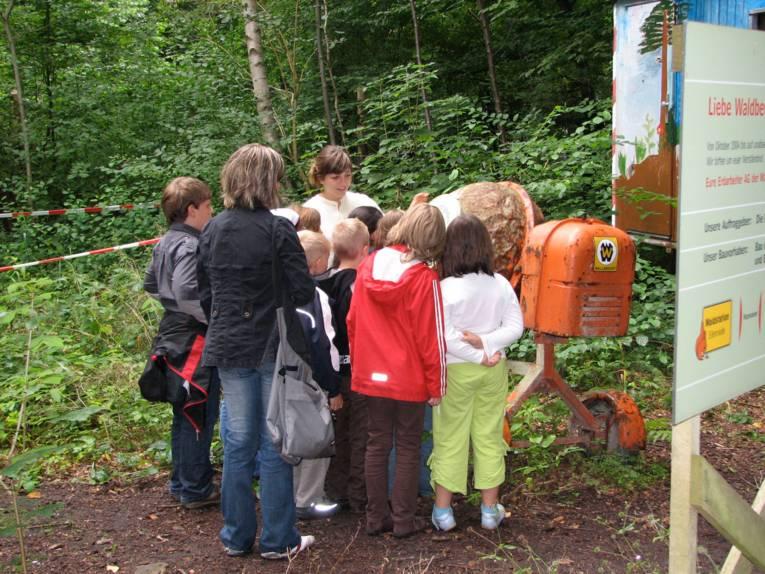 Kinder und Betreuerinnen vor Betonmischer stehend