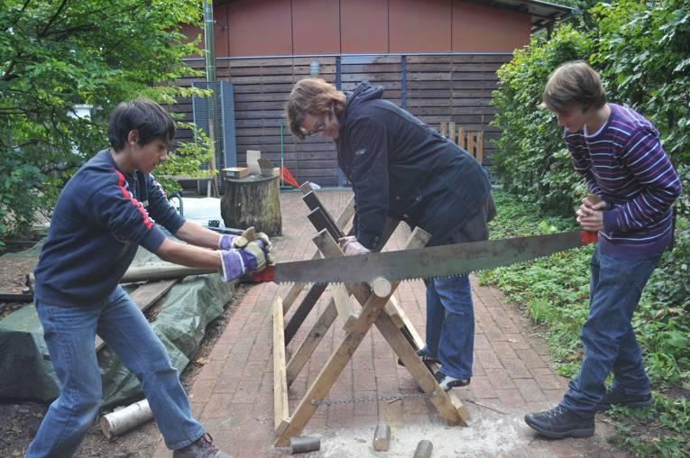 Jugendliche bei Sägearbeiten